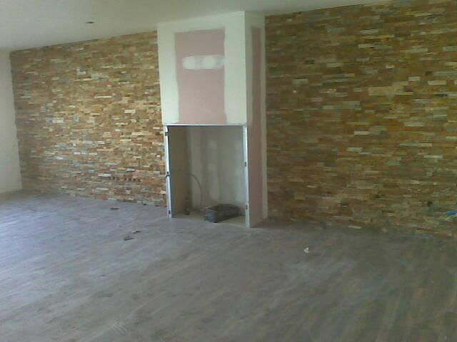 Parede da sala comum revestida a pedra e o recuperador de calor ...